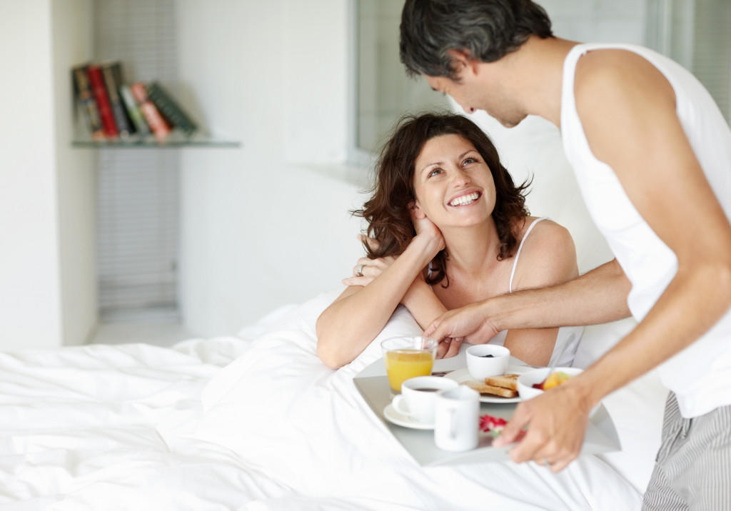 Mature man serving breakfast for his wife in bed at home