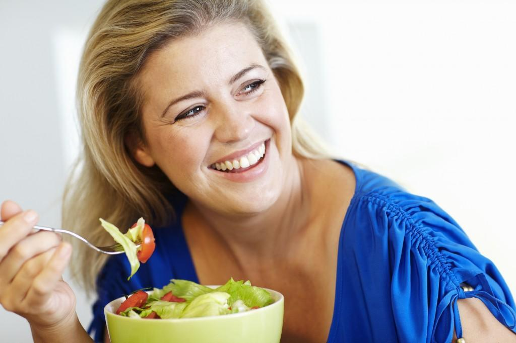 Smiling woman eating salad at table